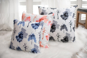 picture of white, blue, red, and black trees on fabric sitting in a clean white modern sleek room