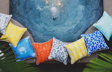 picture of pillows made with outdoor pool beach summer fabric sitting beside hot tub