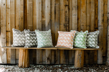 Photo of pillows made with modern chevron style pattern fabric sitting on wooden bench next to barn