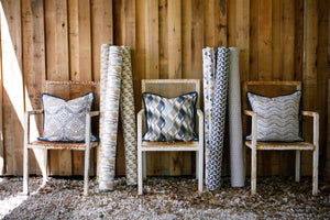 photo of mid western desert style fabrics with mountains, alpacas, cacti, cactus sitting in chairs next to old barn wood wall