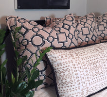 photo of bedding and pillows made with modern contemporary pink boho inspired fabric