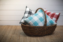 photo of pillows made with large plaid pattern outdoor fabric sitting in basket