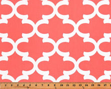 Photo of coral Quatrefoil trellis pattern printed on white fabric