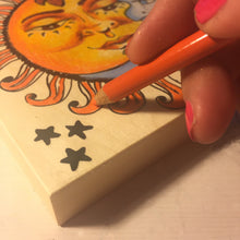 Close up showing corner Sun Moon NicheBoard artist working in colored pencil