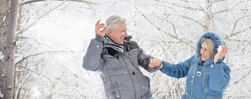 Senior couple fighting with snow