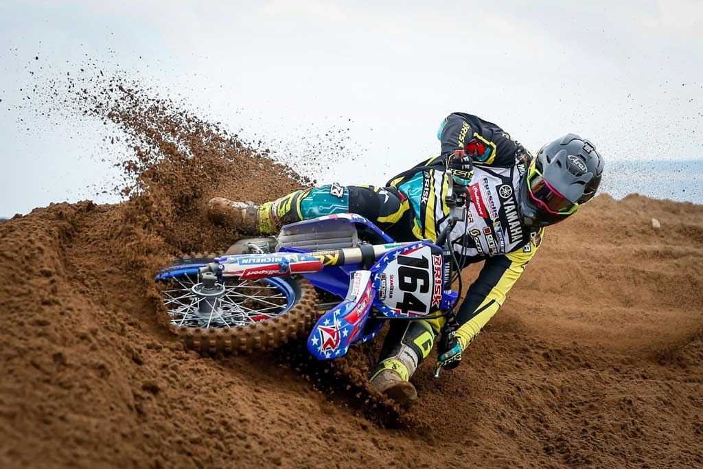 164 motocross racer turning hard into a burm corner wearing full risk racing mx gear including jersey pants and gloves