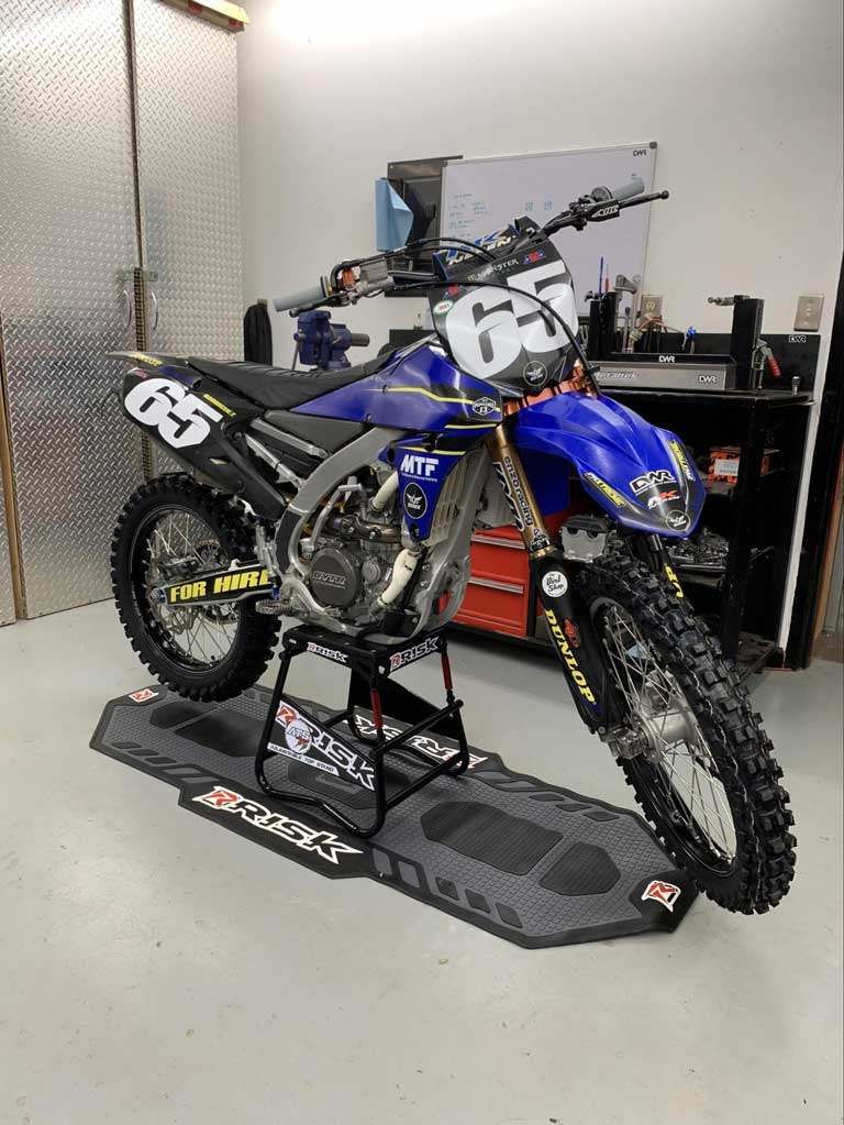 #65 blue dirt bike in a garage sitting on Risk Racing's ATS MX stand and pit mat