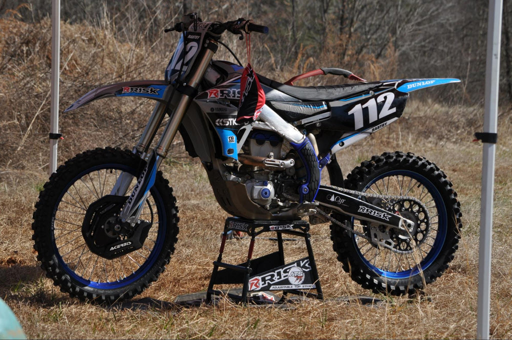 MX bike num 112 sitting on a Risk Racing ATS adjustable top stand in the grass under a canopy