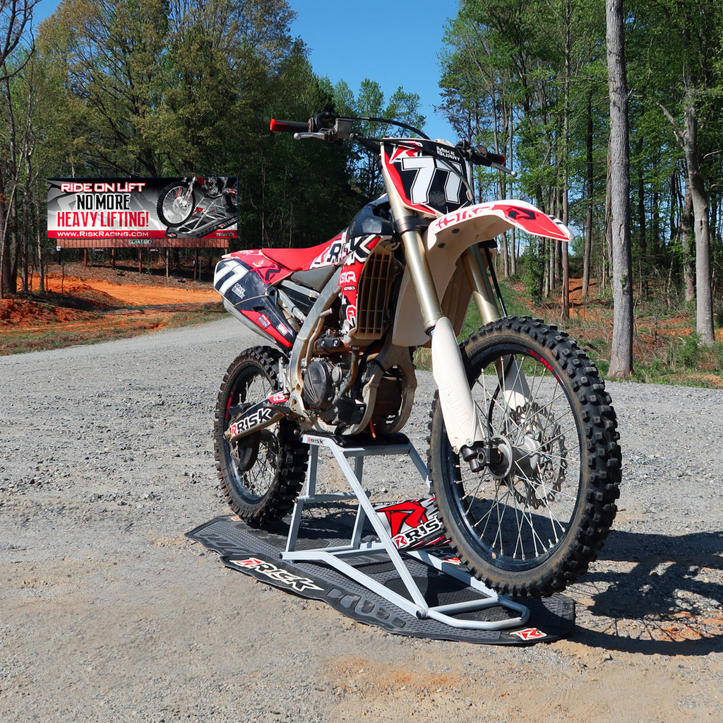 MX bike num 77 sitting on a RR1 Ride on mx lift stand on top of a pit mat all covered in Risk Racing emblems