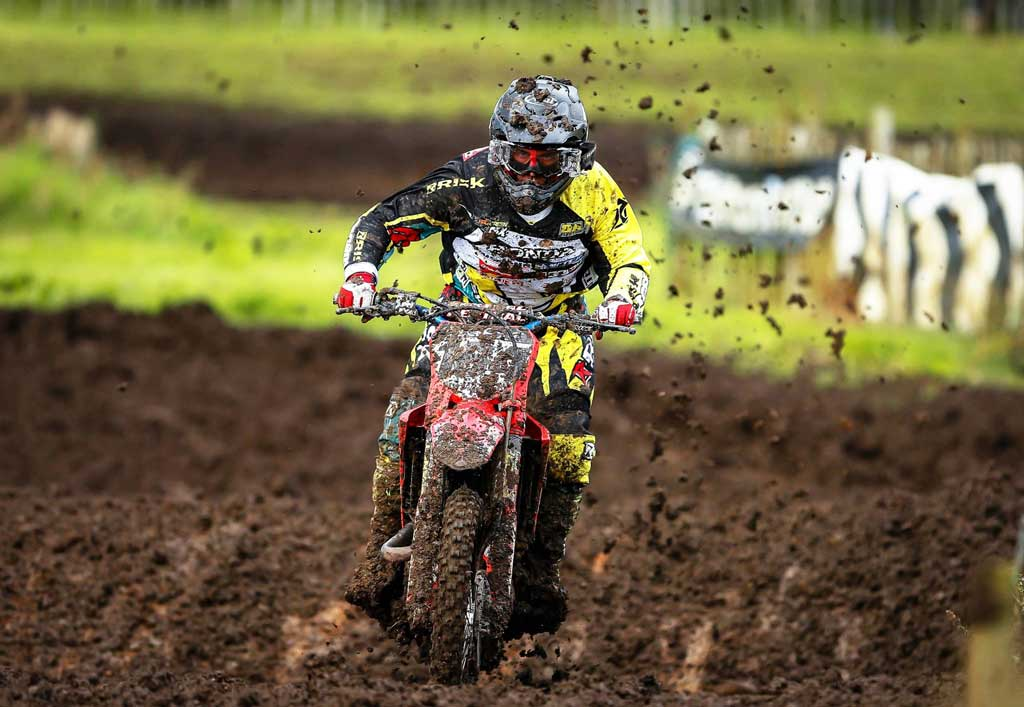 Motocross racer coming straight at camera through heavy mud wearing black and yellow Risk Racing moto gear