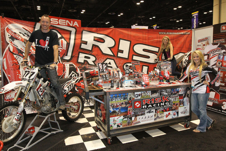 Risk Racing booth at the SENA show full of products including RR owner James Burry posing on a dirt bike sitting on a RR1 stand