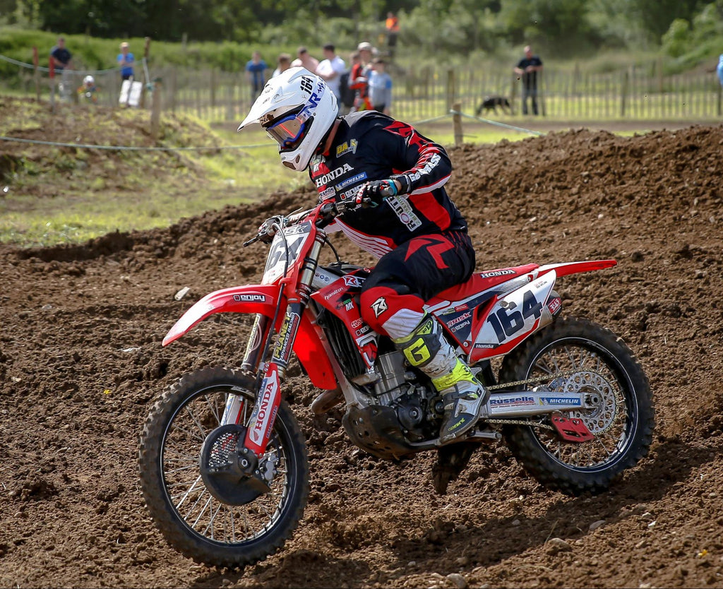 Risk Racing's mx number 164 red Honda wearing red n black RR jersey pants and gloves out on the track