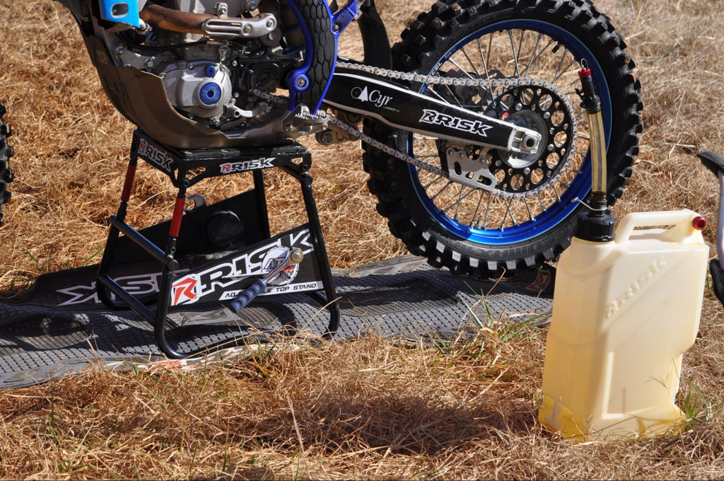 Risk racings EZ utility jug w fuel near dirt bike on ATS stand and pit mat by RR
