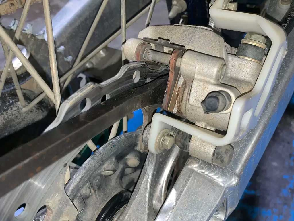 close up of a dirt bike brake system showing rotors pads and pistons