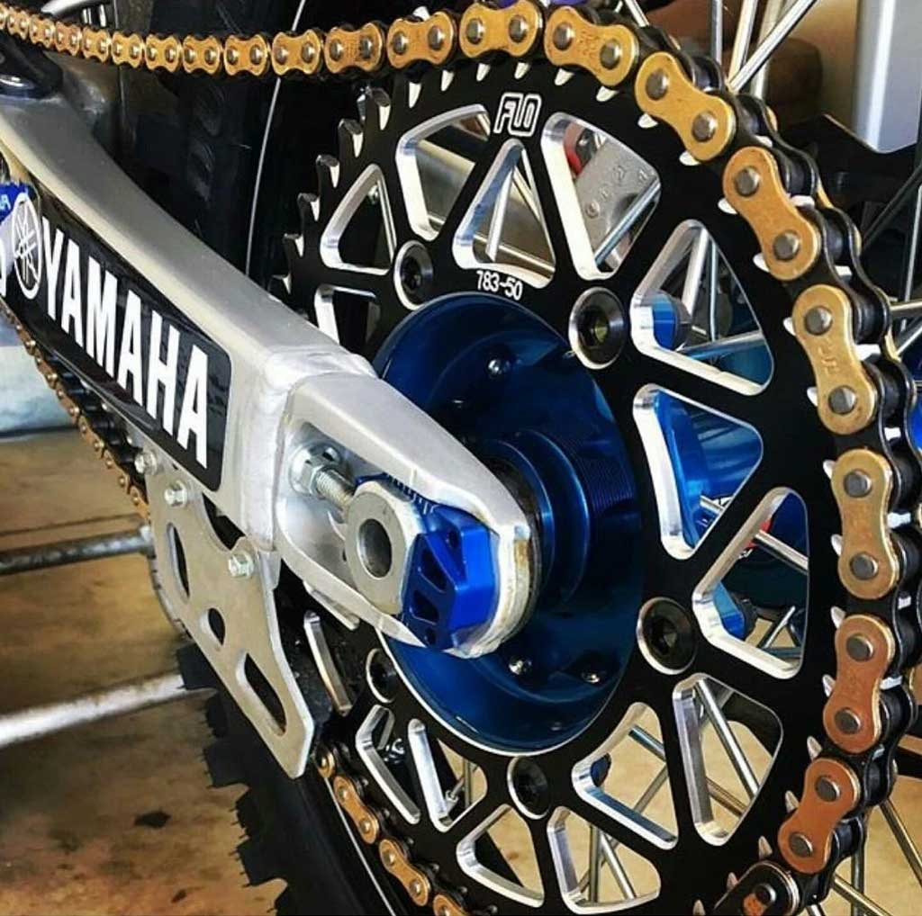 close up of a swing arm sproket and chain of a very clean dirt bike