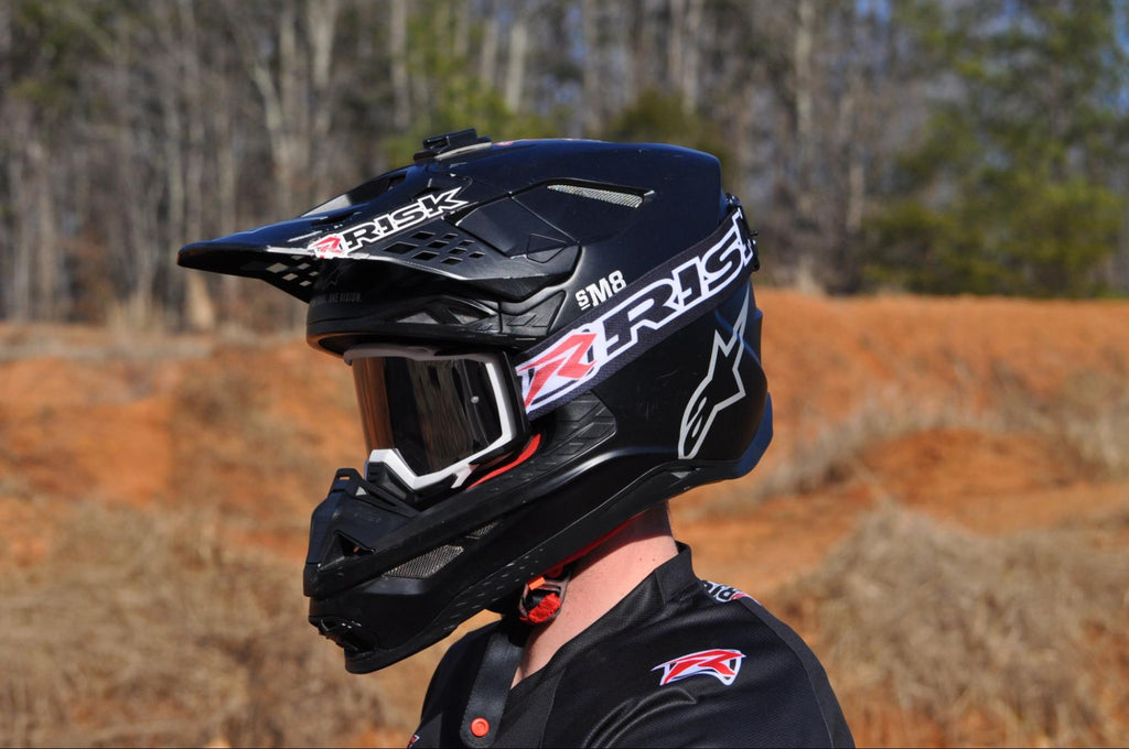 dirt biker wearing black helmet Goggles and jersey by Risk Racing hills tress in the background