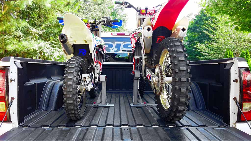 dueling dirt bikes both secured into the back of a rhino lined pickup bed using lock n load pros by Risk Racing