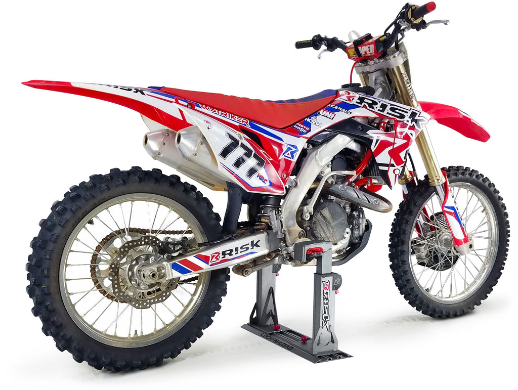 white studio pic of a motocross dirt bike secured into a lock n load pro transport system by Risk Racing