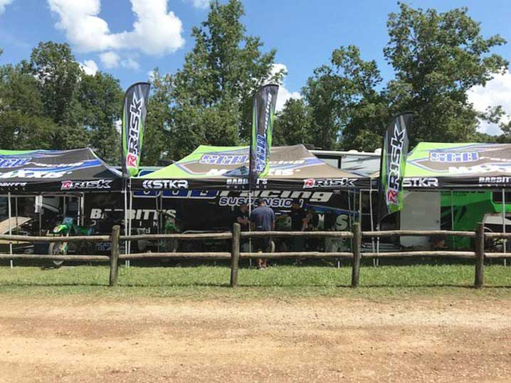 motocross pit row featuring pit canopies from Risk Racing and STKR