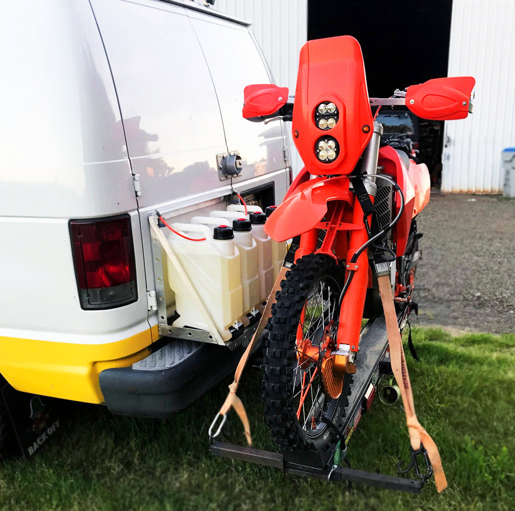 motovan carring multiple ez utility fuel jugs by risk racing and a dirt bike on a hitch mount platform
