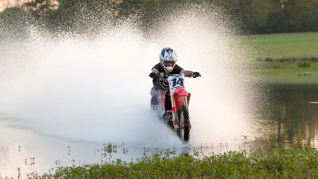 mx number 14 exiting a lake onto the shore surrounded by white water splash
