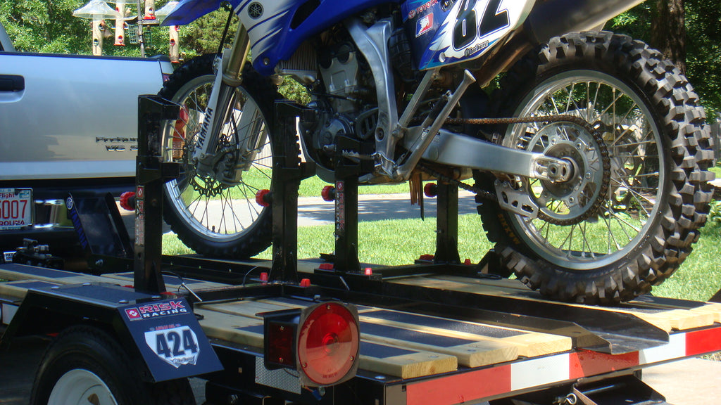 mx bike number 82 secured onto a tiny moto trailer via a lock n load by Risk Racing