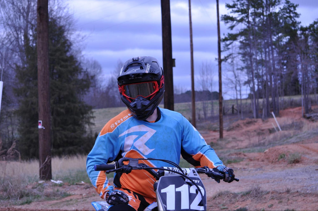 mx num 112 person sitting on dirt bike wearing blue and orange risk racing jersey land n tress in BG