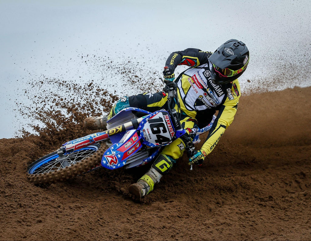 mx num 164 Risk Racing Pro Rider wearing RR jersey pants n gloves while hitting the top of a berm turn