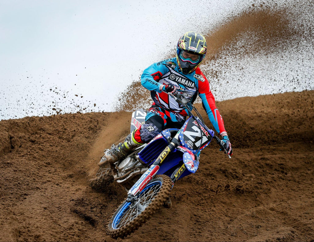 mx num 21 Risk Racing pro rider wearing full RR race gear throwing roost coming out of a berm turn