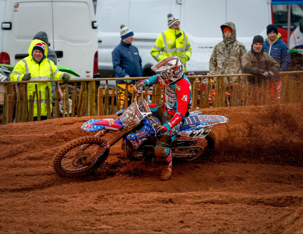 mx number 22 Risk Racing pro rider (in full Risk Racing gear including jersey, pants, and gloves) taking a very muddy corner on a rainy track day