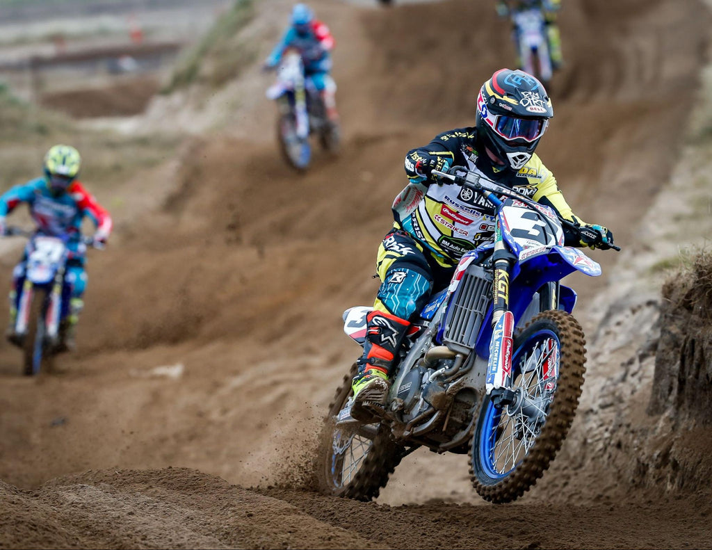 mx number 3 Risk Racing pro rider (in full Risk gear) exiting a rhythm section of a track w opponents in the background