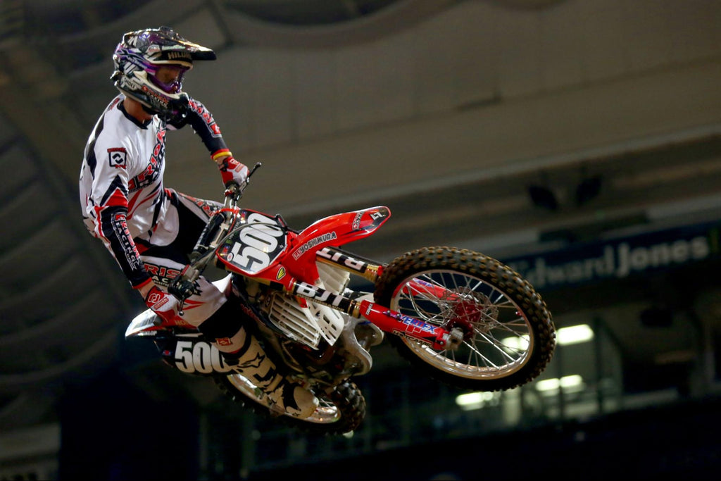 mx number 500 Risk Racing Pro rider wearing RR Jersey pants n gloves whipping high up in the air stadium roof in BG