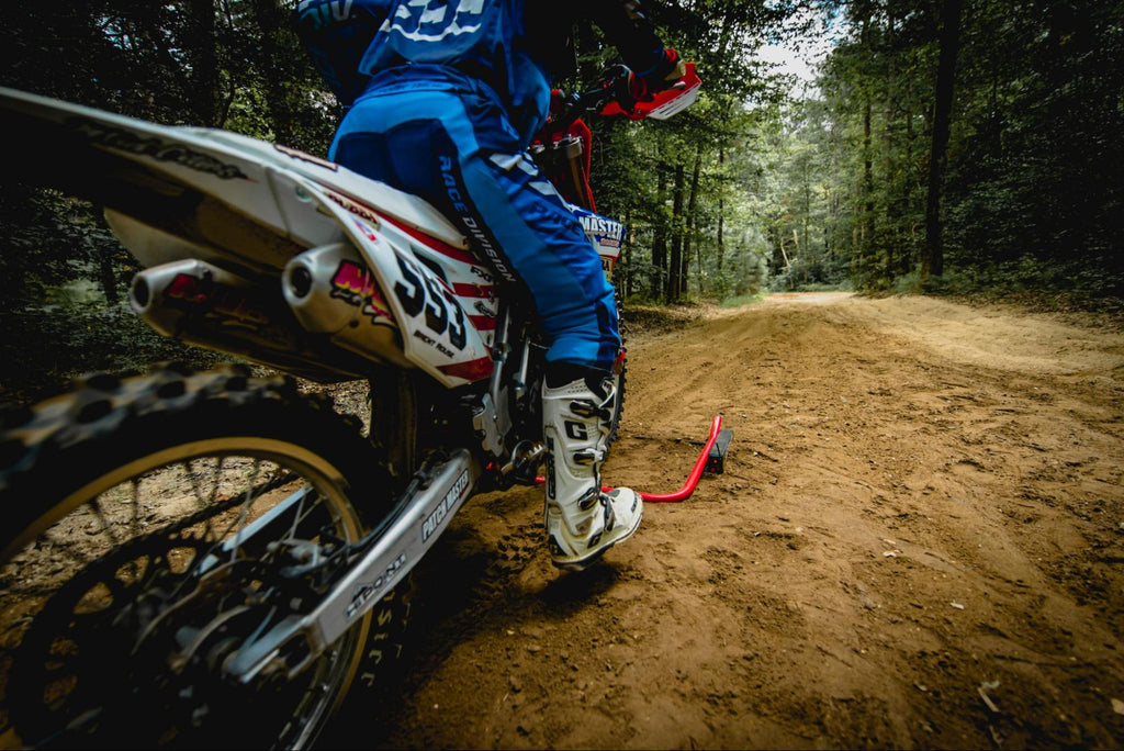motocross number 553 practicing take offs with a holeshot race gate by Risk Racing on a dirt road in forest area
