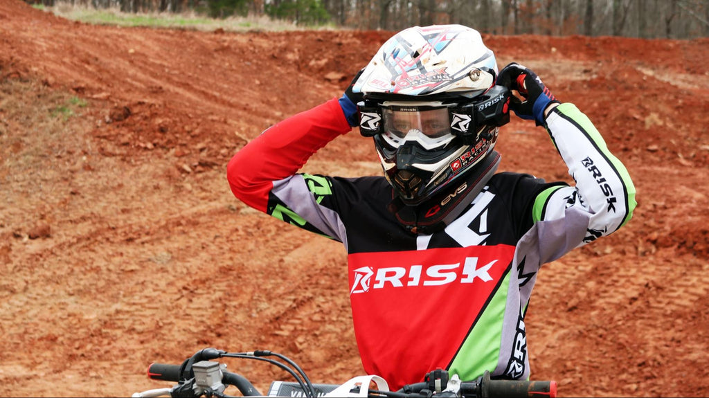 mx num 77 Mike Burry checking his Risk Racing goggles wearing an RR jersey and RR auto roll off track dirt BG