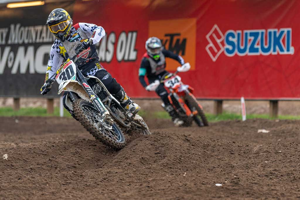 num 30 navigating a turn during a motocross race with num 34 close behind