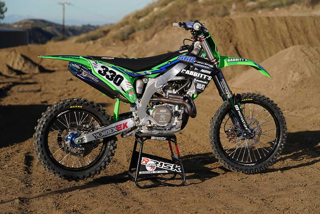 num 330 motocross bike sitting on an ATS adjustable top magnetic stand by Risk Racing outside in the dirt