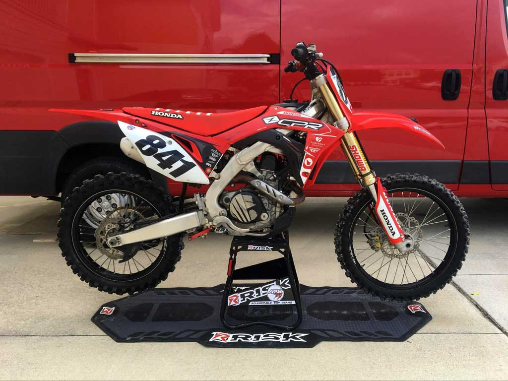 num 841 red honda dirt bike sitting on an ATS stand and pit mat by Risk Racing red motovan in the background