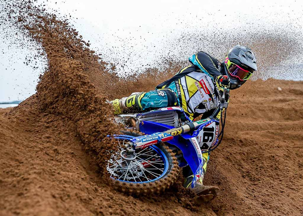 num_164_Risk_Racing_factory_racer_tearing_into_the_top_of_a_burm_turn_throwing_dirt_in_a_wave