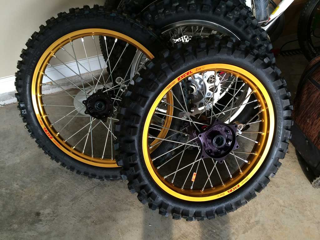 a pile of dirt bike wheels and tires in a garage