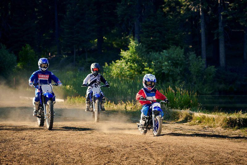 three different sized dirt bikes and their riders driving on a dirt road towards camera forrest in BG