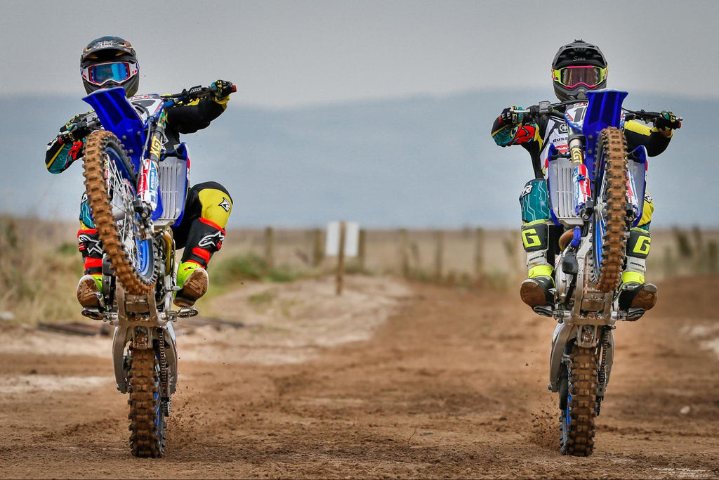 two risk racing pro riders wheelieing high up directly at camera