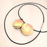 a light orange and coral coloured peach locket open. stung onto a faux leather cord 1mm