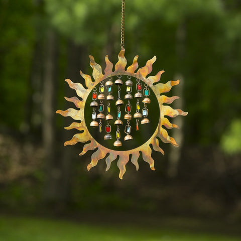 A colorful wind chime featuring enamel bells and a sunburst.