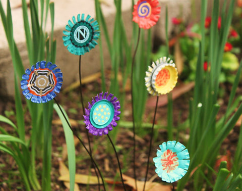 Metal flowers made from old, painted bottles caps are staked in a flower bed.
