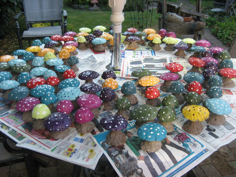 DIY Concrete Mushrooms, painted in many bright colors, sprawled out on a table.