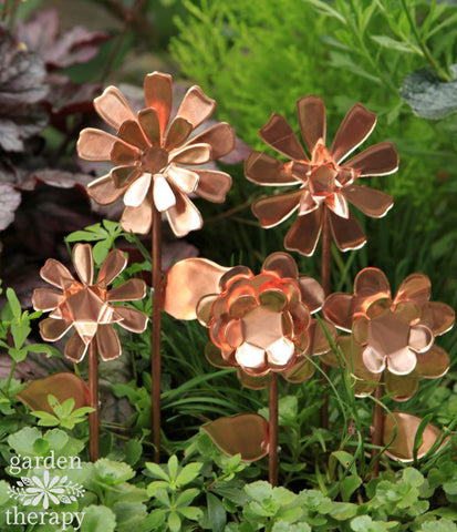 5 handmade, copper flowers are staked into a green garden.