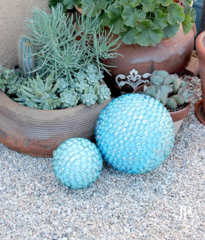 Garden orbs covered in blue glass beads sit in a rocky, outdoor area.