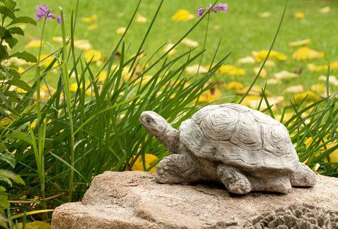 A stone sculpture of a turtle sits atop a rock in a grassy, flowered field.