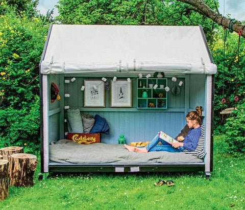 A child reads in a small garden shed converted into a reading nook.