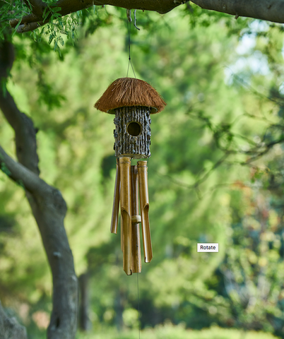 A classic wind chime in a leafy backdrop.